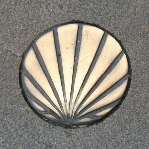 Das Muschelsymbol im Boden des Weges