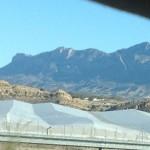 Vorne die Gewächshäuser, hinten schroffe Bergehöhen